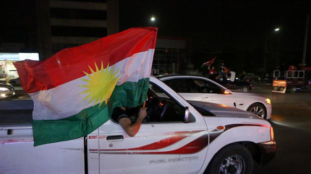 Iraqi Kurdish men celebrate after the polls closed in the controversial Kurdish referendum (AP)