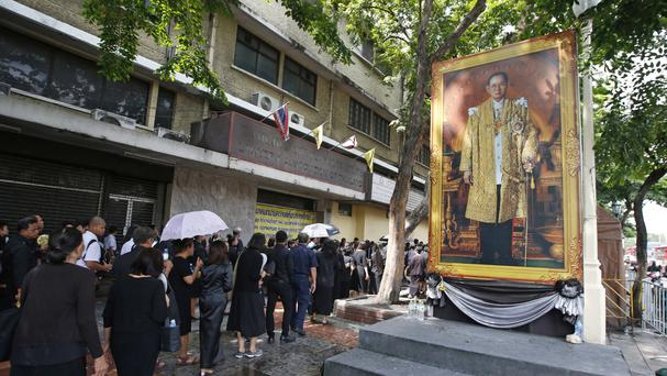 Thai mourners line up beside of portrait of late king Bhumibol Adulyadej (AP)
