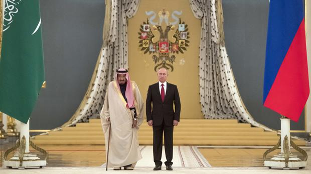 Vladimir Putin, right, and Saudi King Salman listen to national anthems during their meeting in the Kremlin (AP)