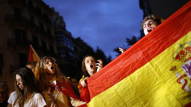 Anti-independence demonstrators waving Spanish flags in Barcelona (AP)