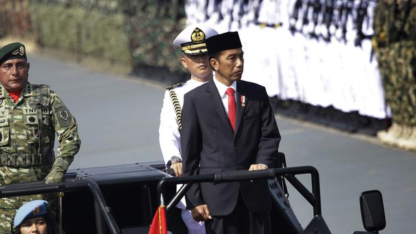 Indonesian president Joko Widodo inspects the troops during a parade on Thursday (AP)