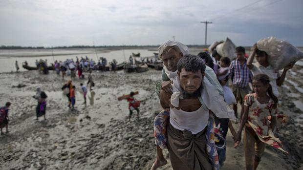 A Rohingya from Burma carries an elderly woman after they crossed the border into Bangladesh (AP)