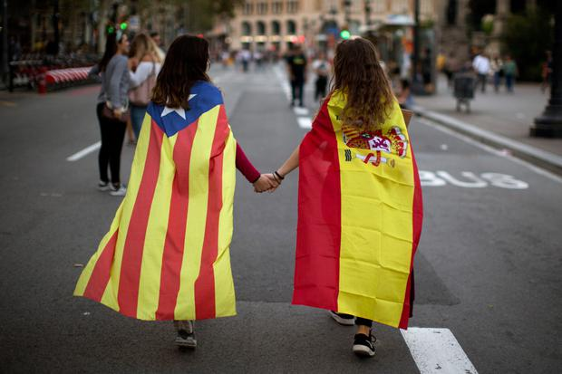 Irene Guszman (15) wearing a Spanish flag on her shoulders and Mariona Esteve (14) with an 'estelada' or independence flag, walk along the street to take part in a demonstration in Barcelona, Spain, on Tuesday. Thousands of people demonstrated against the confiscation of ballot boxes and charges on unarmed civilians during Sunday's referendum on Catalonia's secession from Spain that was declared illegal by Spain's Constitutional Court. Photo: Emilio Morenatti