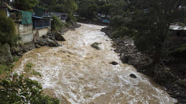Water flows through an engorged river caused by the heavy rains brought by Tropical Storm Nate, on the outskirts of San Jose, Costa Rica (AP Photo/Moises Castillo).