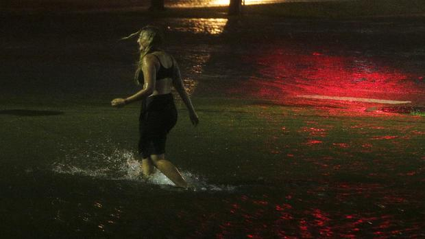 A woman wades through flooded Water Street in Mobile, Alabama (AP Photo/Brynn Anderson)