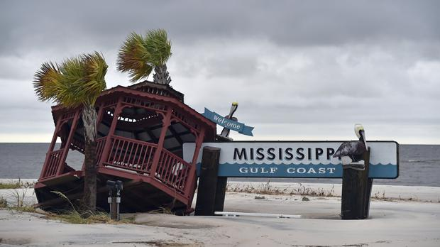 A gazebo is blown over the Mississippi Gulf Coast welcome sign near the intersection of Hewes Avenue and US 90 in Gulfport (Justin Sellers/The Clarion-Ledger via AP)