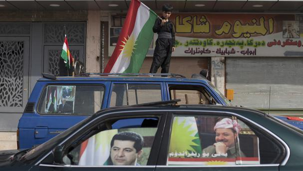 File photo of a boy carrying a Kurdish flag on top of a car with pictures of Kurdish president Masoud Barzani and his son Masrour on the windows, in the disputed city of Kirkuk (AP)