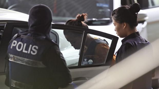 Siti Aisyah, one of the female suspects on trial over the killing of North Korean leader Kim Jong Un's brother, Kim Jong Nam, is escorted by police as she leaves court on Tuesday. (AP Photo/Sadiq Asyraf)