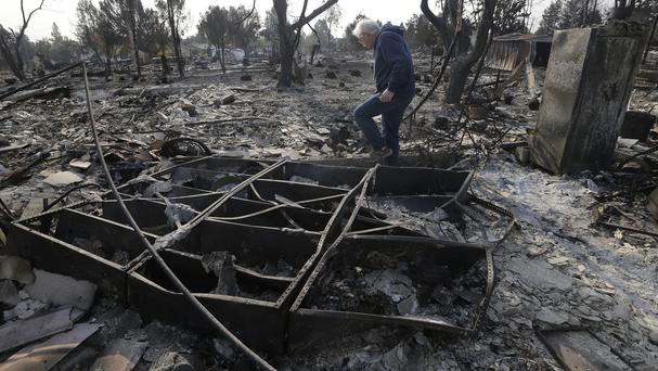 Phil Rush walks through the burnt remains at the site of his home destroyed by fires in Santa Rosa (Jeff Chiu/AP/PA)