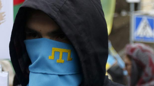 File photo of an activist masked by a scarf with a Crimea Tatar symbol attending a rally against the Russian annexation of Crimea (AP)