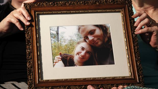 Mothers Linda Boyle and Lyn Coleman hold a photo of their married children, Joshua Boyle and Caitlan Coleman (AP)