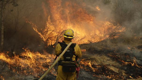 Some 9,000 firefighters are working to control the flames using air tankers, helicopters and more than 1,000 fire engines (AP)