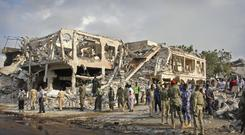 Somali security forces and others gather and search for bodies near destroyed buildings at the scene of Saturday's blast (AP)