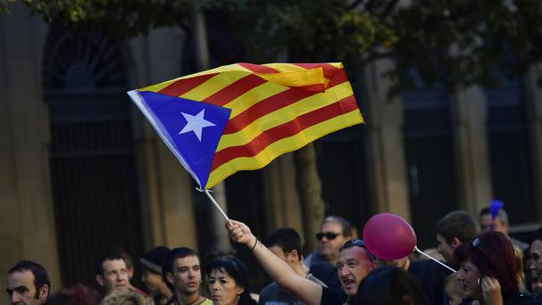 A pro-independence supporter holds up an ''estelada'' or Catalan pro independence flag during a rally (AP/Alvaro Barrientos)