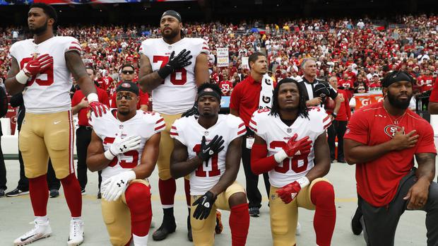 Member of the San Francisco 49ers kneel and stand during the playing of the national anthem (AP)