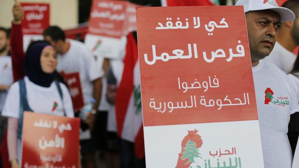 Lebanese hold placards during a protest calling for the departure of Syrian refugees from Lebanon (AP)