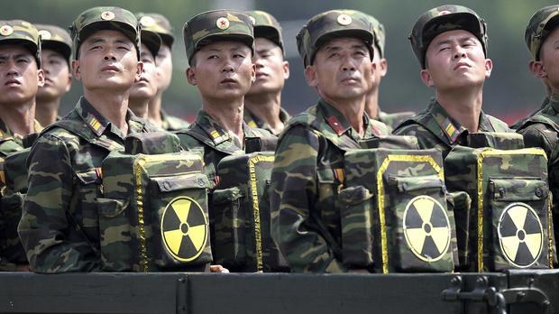 North Korean soldiers carrying packs marked with the nuclear symbol (Wong Maye-E/AP)