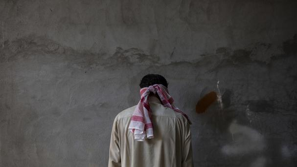 A blindfolded IS suspect faces away from security officers at a Kurdish screening centre (AP/Bram Janssen)