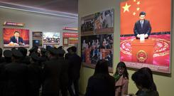 Military officers and Communist Party members walk by photos of Chinese President Xi Jinping at an exhibition highlighting China's achievements under five years of his leadership (AP)