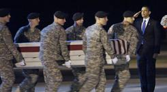 Then president Barack Obama salutes the remains of a fallen US soldier at Dover Air Base, Delaware (AP)