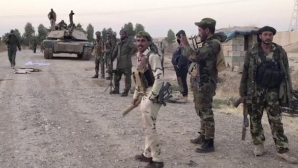This image made from a video shows Iraqi soldiers in the Qatash area south of Kirkuk, Iraq (APTN via AP)