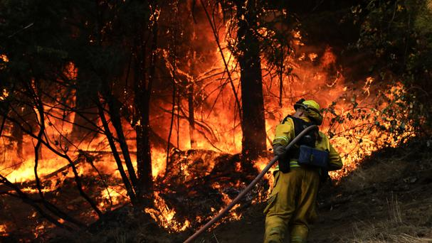Firefighter tackles blaze along a California highway (AP photo/Jae C. Hong)