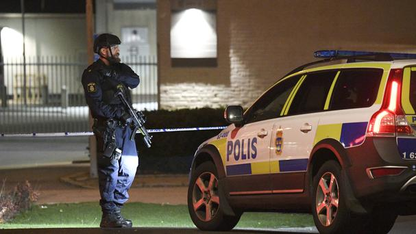 A police officer stands guard outside a cordoned-off area surrounding a police station in Helsingborg (TT News Agency/AP)