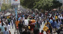 Protesters march near the scene of Saturday's massive truck bomb attack in Mogadishu (AP)