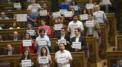Legislators hold up posters reading: