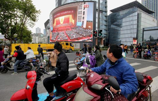 People watch a broadcast of Chinese President Xi Jinping delivering his speech during the opening of the 19th National Congress of the Communist Party of China, on a giant outdoor screen in Nanjing, Jiangsu province, China. Photo: Reuters