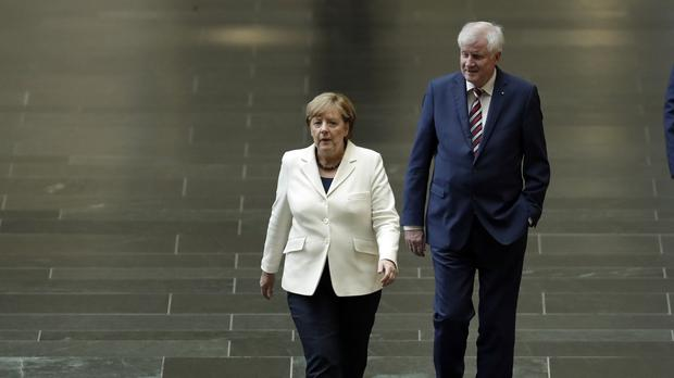 German chancellor and chairwoman of the Christian Democratic Union party Angela Merkel and Horst Seehofer, chairman of the Christian Social Union party, right, arrive for a meeting at a Reichstag (AP)