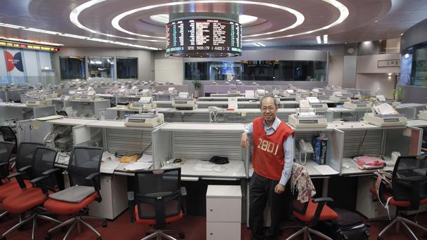 Yip Wing-keung, a trading manager at local brokerage Christfund Securities, wearing his red trading jacket, poses for a photo at the Hong Kong Stock Exchange before its closure (AP)