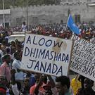 Protest placards reading Out al Shabab, left, and Oh God, have mercy on the dead near the scene of an earlier truck bombing in Mogadishu (AP)
