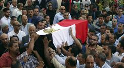 People carry the coffin of police captain Ahmed Fayez who was killed in a gunfight in al-Wahat al-Bahriya area in Giza province, during his funeral in Cairo (AP Photo/Alaa Elkassas)