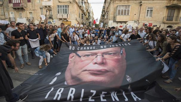 A banner with a photo of Malta police commissioner Lawrence Cutajar outside the Malta police headquarters after a rally to honour Daphne Caruana Galizia (AP Photo/Rene Rossignaud)