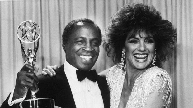 Robert Guillaume, star of Benson, gets a hug from Linda Gray of Dallas who presented him with the Emmy (AP)