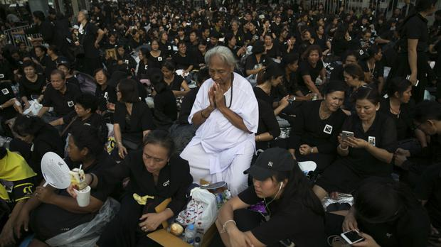 Mourners pray for the late King Bhumibol Adulyadej as they take part in the cremation ceremony in Bangkok (AP)