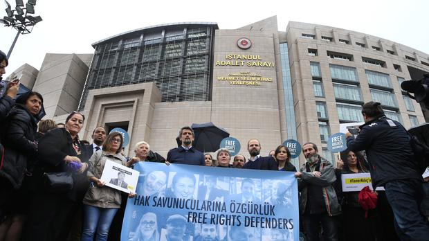 Protesters outside a court in Istanbul as 11 human rights activists go on trial accused of belonging to and aiding terror groups (AP Photo/Lefteris Pitarakis)