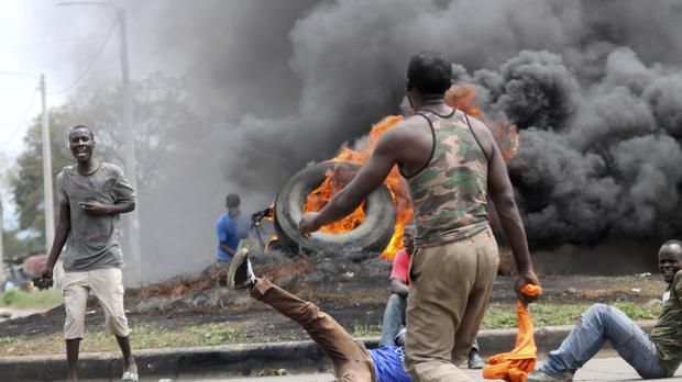 Opposition supporters burn tyres and barricade roads as they confront police in Kisumu (AP)