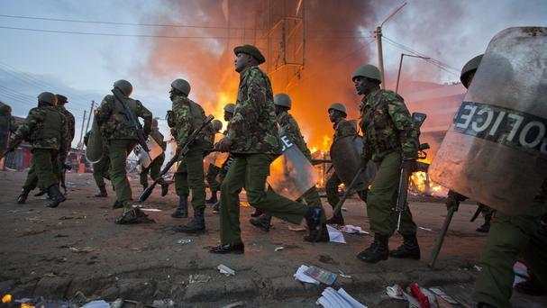 Police move past burning shops during clashes in Nairobi (AP)