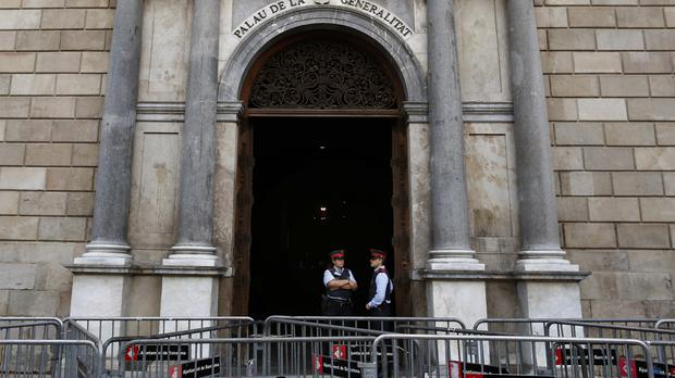 Catalan police officers stand guard at the entrance of the Palau Generalitat in Barcelona (AP)
