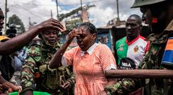 Policemen help a schoolgirl who inhaled tear gas fired as the police were trying to hold off a group of opposition supporters in Nairobi yesterday. Photo: Getty
