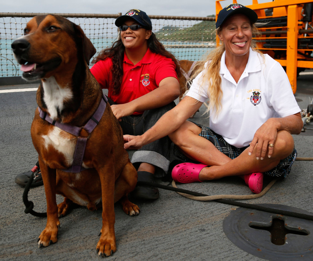 Jennifer Appel (right) and Tasha Fuiava sit with their dogs on the deck of the USS Ashland. Photo: AP
