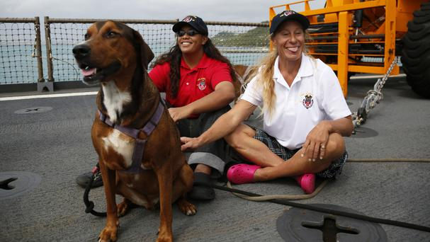 Tasha Fuiava and Jennifer Appel with their dogs on the deck of the USS Ashland (AP)