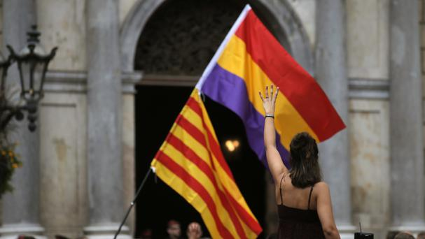 A pro-independence demonstrator holds up four fingers symbolising the four stripes of the Catalonian flag during a demonstration in Barcelona, Spain (AP/Manu Fernandez)