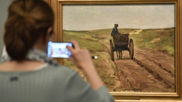 A visitor takes a picture of a paining by Max Liebermann at the exhibition Gurlitt: Status Report in Bonn, Germany (AP/Martin Meissner)