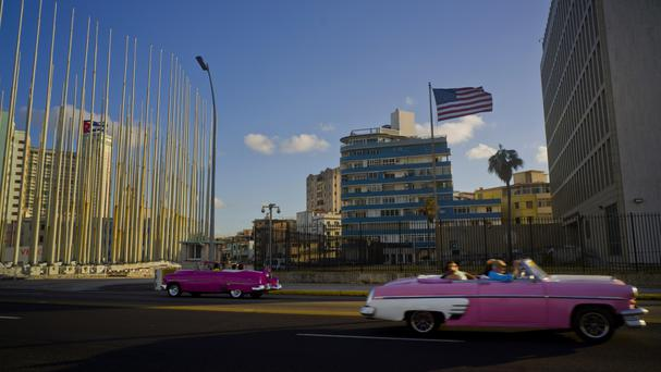 Tourists ride in classic American convertible cars past the United States embassy, right, in Havana, Cuba. (AP Photo/Ramon Espinosa, File)