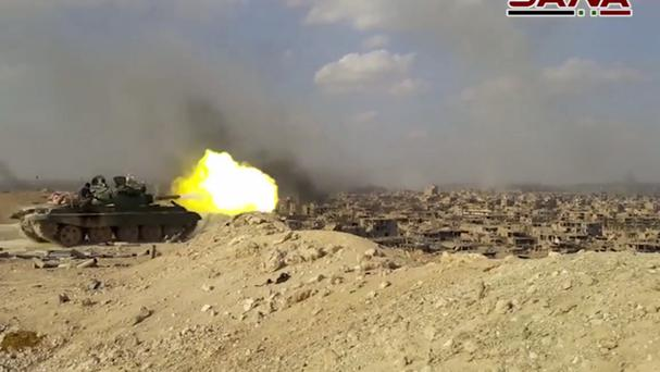 Screengrab from a video showing a Syrian tank firing during the battle against Islamic State militants in Deir el-Zour, Syria (Sana/AP)