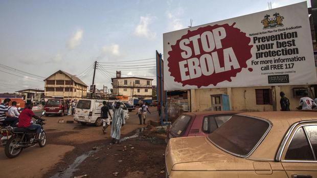 People pass a banner reading 'STOP EBOLA' forming part of Sierra Leone's Ebola free campaign in Freetown (AP)