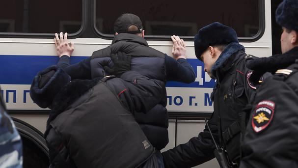 Police search a man during the protest in Moscow (AP/Nikolay Koreshkov)